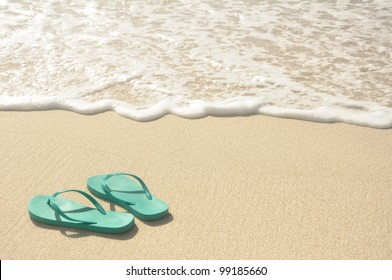 Green Flip Flops on a Sandy Beach