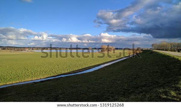 Green floodplains of the river Rhine. The Netherlands, winter 2019. Fluvial landscape, moraine hills Utrecht Hill Ridge in background
