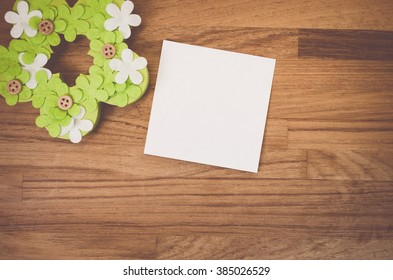 green flower easter decoration and blank memo on a wood surface - copy space