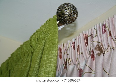A green and flowery drapery with it's finials accessories and beautiful hardware.