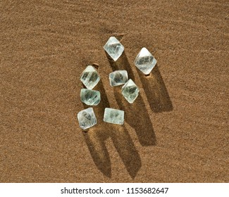 Green Fluorite Natural Octahedron Crystals on the beach at sunrise.