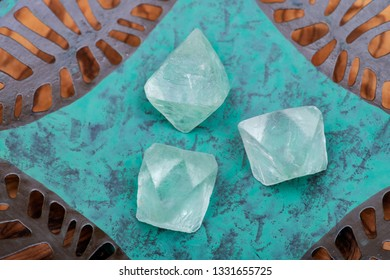 Green Fluorite Natural Octahedron Crystals on copper green decorative plate.