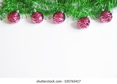 Green foil garland with beautiful red Christmas ball. Xmas home decoration. Festive flat lay background. New Year elegant decor. Stock photo for design greeting card and banner. Copy space