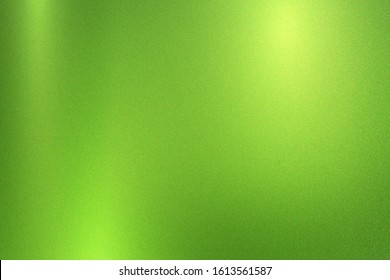 Green foil metallic wall with glowing shiny light, abstract texture background