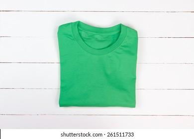 Green folded t-shirt on white wooden background
