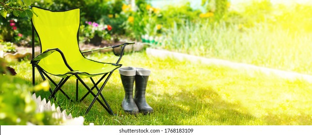 Green folding textile chair for rest and rubber boots on grass in garden at summer day, nobody