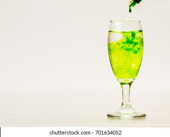 Green food coloring diffuse in water inside wine glass with empty copyspace area for slogan or advertising text message, over isolated grey background.