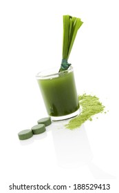 Green food supplement. Spirulina, chlorella and wheatgrass. Green juice, green pills, wheatgrass blades and ground powder isolated on white background. Healthy lifestyle.