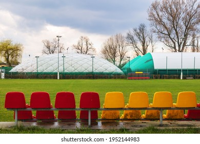 Green football field from side view with red and yellow chairs and cloudy sky