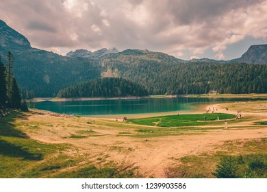 Green forest and blue lake with silver clouds near Zabljak , Montenegro