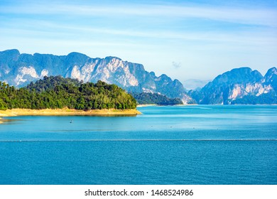 Green forest and limestone mountain range in the blue lake at Rajjaprabha Dam in Suratthani, Thailand.