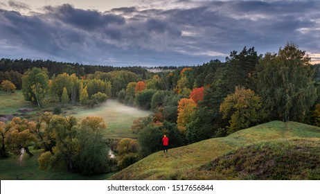 Green forest turning into autumn colours at evening with fog and person in red jacket.
