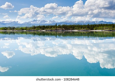 Green forested hills, snowcapped mountains and clouds at Lake Laberge, Yukon Territory, Canada are mirrored on water surface on beautiful summer day