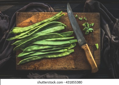 Green french beans on rustic cutting board with kitchen knife on dark wooden background, top view.  Legumes vegetables