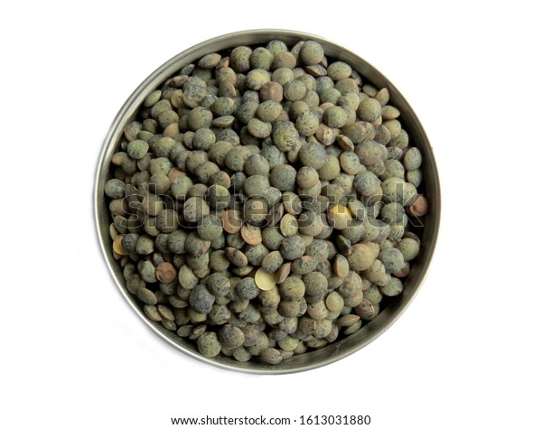 Green french lentils in a round container on white