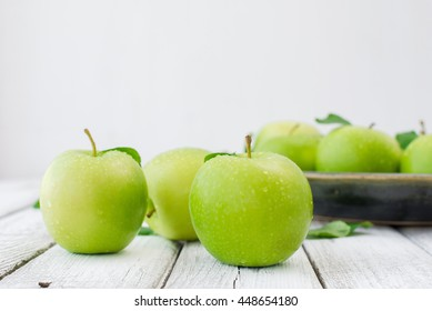 Green fresh apples on wooden table close up, rustic style, selective focus