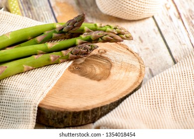 Green fresh asparagus on wooden plate background