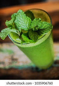 green fresh detox juice with peppermint on a vintage wooden table