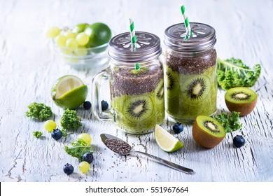 Green fresh detox vegan superfoods smoothie, vitamins diet drink with kale, chia seeds, lime, kiwi, blueberries.