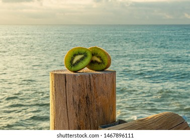 A green and fresh green kiwi cut in half on a rustic wooden dock with sea on the background - Freshly harvested kiwi - Blue water