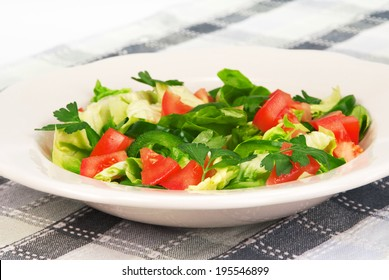 Green fresh salad in a rustic plate served on a checked tablecloth