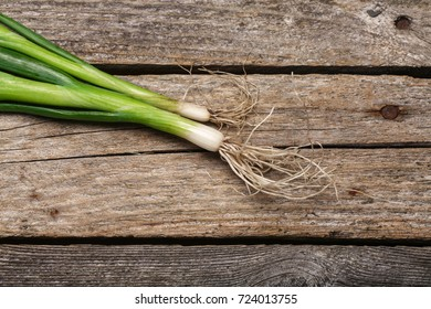 Green fresh spring onion on the vintage wooden table