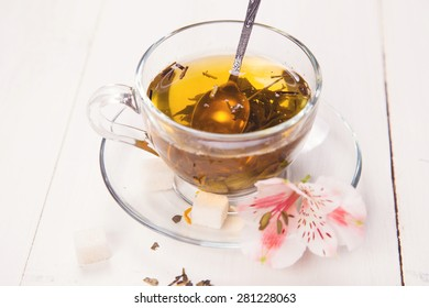 green fresh tea with a spoon, sugar and flower