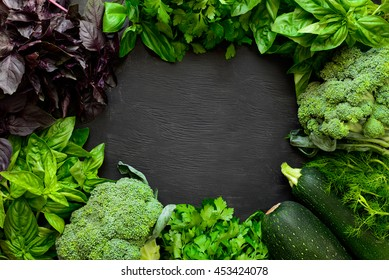 Green fresh vegetables on a black board, organic farm, or local farming or farm market concept, space for a text