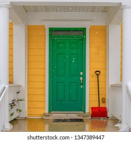 Green front door and red snow shovel in winter