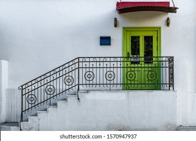 Green front door to a white building with wrought iron railings
