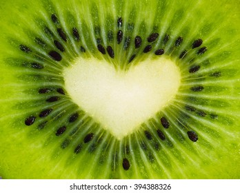 Green fruit kiwi close up with heart, green background. Kiwi fruit in the form of heart. Kiwi with seeds close-up. Heart using kiwi fruit for Valentine's day. Beautiful kiwi whole screen with heart.