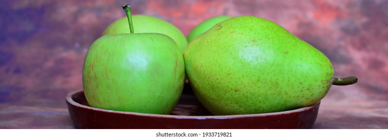 Green fruits, apples and pears on a brown background. Widescreeen panoramic view