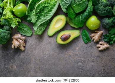 Green fruits and leafy vegetables arrangement simbolising vegetarian or healthy alimentary products for keeping detoxifying or getting skinny diet, flat lay template with a space for a text, view from