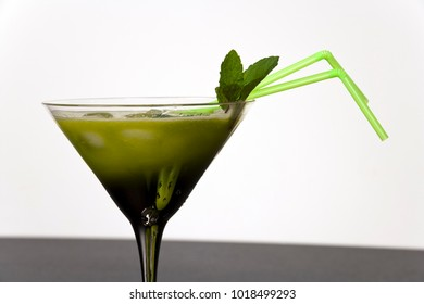 Green fruits and vegetables juiced in cocktail glass with a sprig of mint