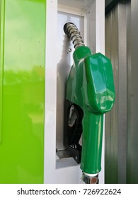 Green Fuel nozzle at oil station.