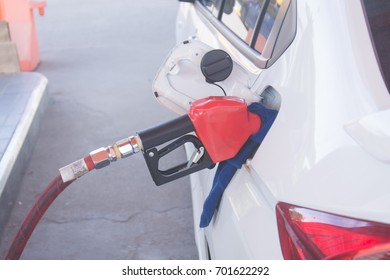 green fuel nozzle to refill fuel in car at gas station.