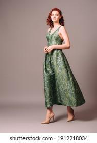 Green full-length evening dress. Beautiful model wearing emerald high heels, modern feminine look for an event. Women's fashion. Adorable lady.