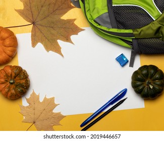 Green fully filled school backpack, pen, pencil, pumpkins and autumn leaves on yellow background with place for text. Top view