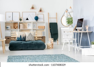 Green futon in teenager's room interior with white chair at desk with computer monitor