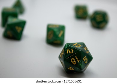 Green gaming dice with gold numbering on a white background. The D20 gaming dice sits in focus in the foreground. These dice are often associated with Dungeons and Dragons and other tabletop games.