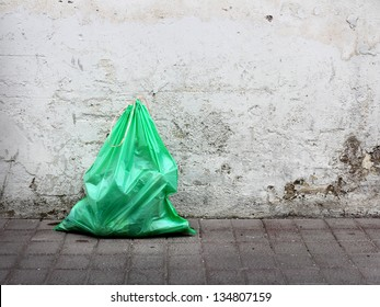 Green garbage bag on street
