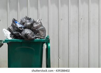 Green garbage bin with black garbage bags.