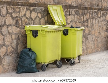green garbage containers near the wall