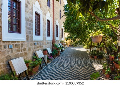 Green garden with medieval ottoman tomb stones in old town in City of Rhodes (Rhodes, Greece)