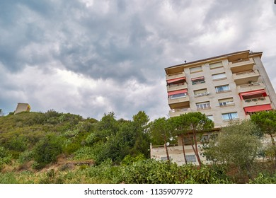 Green garden and multi-storey house in the background of a cloudy sky in the afternoon in Calella, Spain.