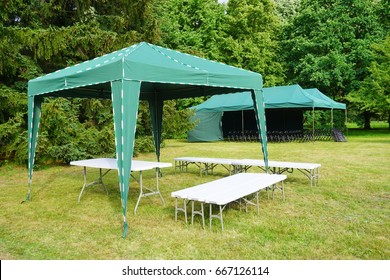 Green garden tent, garden pavilion. Rest area with  chair and picnic tables and green tent installed on green lawn in a park
