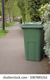 Green garden waste recycling bins in a urban area.
