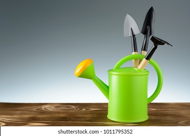 Green garden watering can with tools on a wooden table