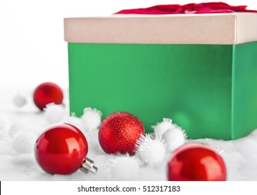 Green gift box for christmas with toys and snow on white background
