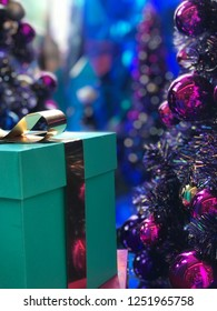 Green gift box with gold ribbon aside metalic purle christmas tree with bokeh backgroung